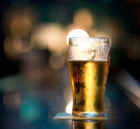 An ice cold beer, set on a coaster on a bar top