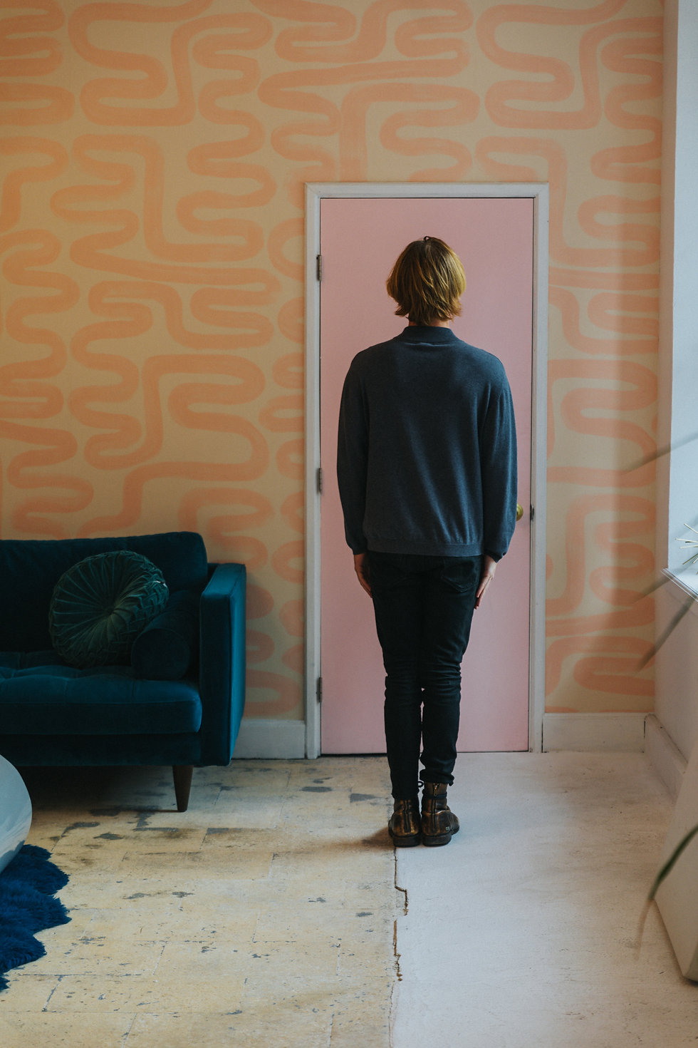 Men wearing black standing in a room covered with peachy wallpaper