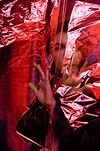 A portrait of a woman behind red cellophane