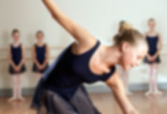Young girl dressed in navy ballet uniform at dance class