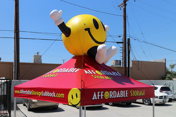 10x10 custom printed pop up tent with happy face inflatable figure