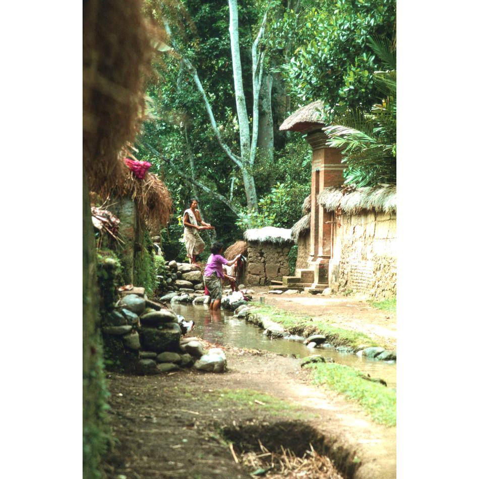 Women washing clothes in village stream.