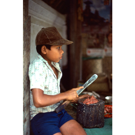 Boy helping to chop meat for temple fesr