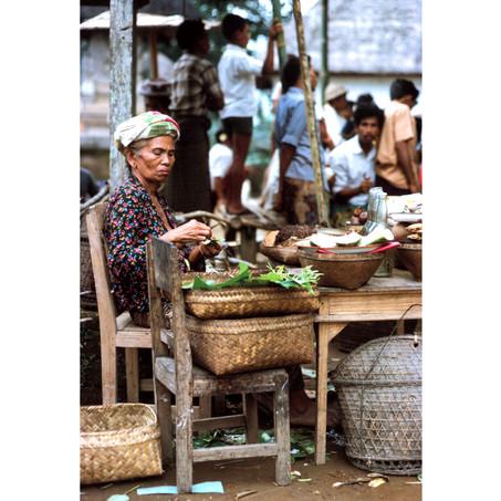 Elderly woman selling wares in village s