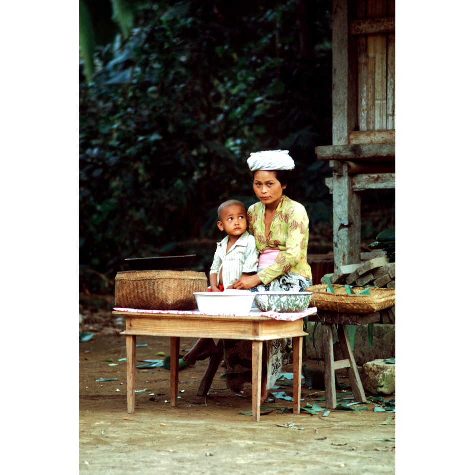 Stall-owner with small boy in village sq