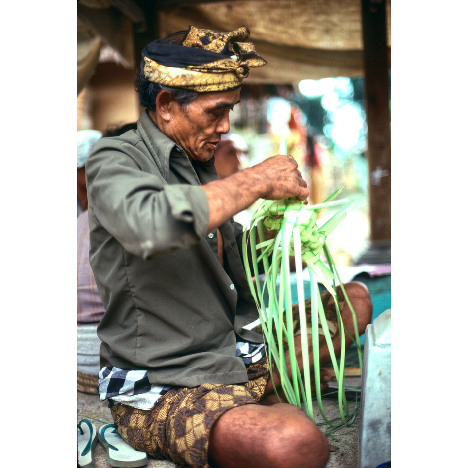 Old actor working coconut leaf for offer