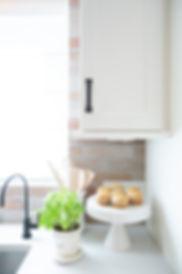 cream kitchen brick backsplash black faucet