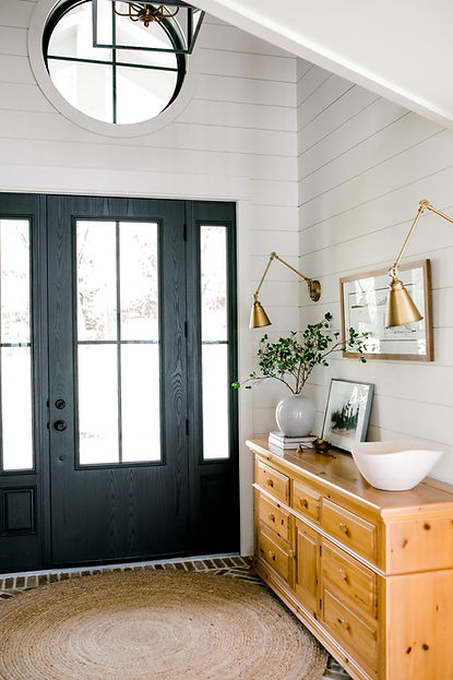 foyer round window entry black door shiplap lantern brick herringbone brass sconces chandelier
