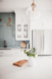 white kitchen blue backplash gold lighting