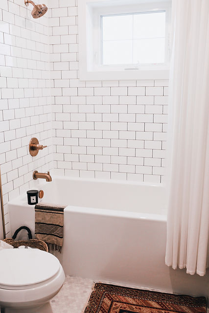 Lisa Clark Design Winnipeg Manitoba Interior Design bathroom white subway tile dark grout gold faucet delta hexagon floor window shower