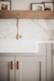 Lisa Clark Design Winnipeg Manitoba interior design green cabinets beams marble tile farmhouse sink brass faucet floating shelf