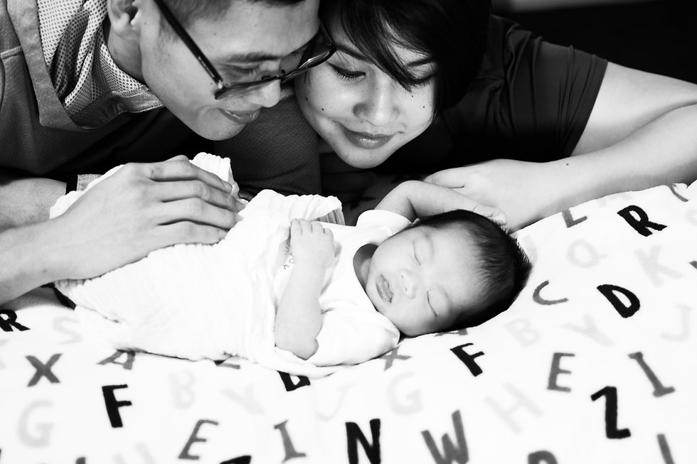 man and woman smiling at baby