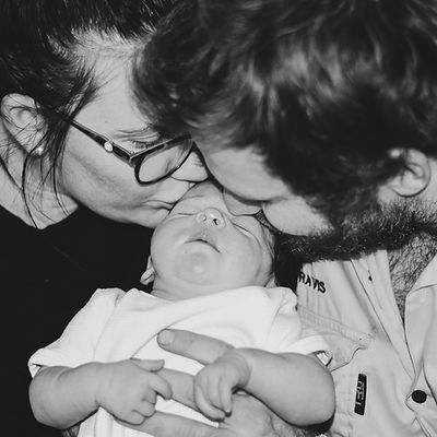 man and woman kissing baby on head
