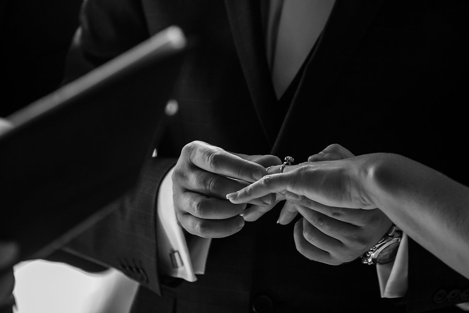 Wedding ring being placed on his brides