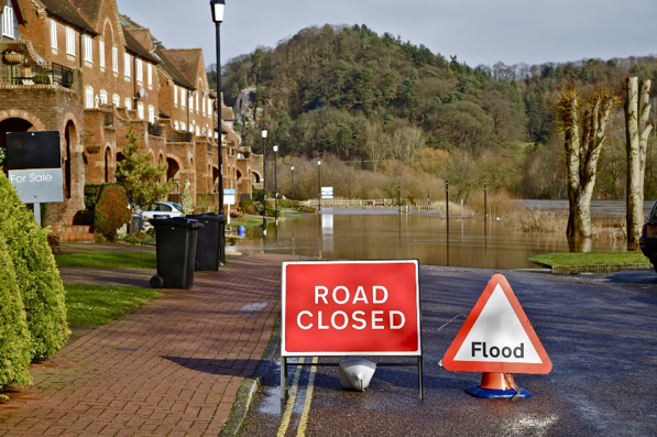 Road closed and flood warning signage on a flooded street