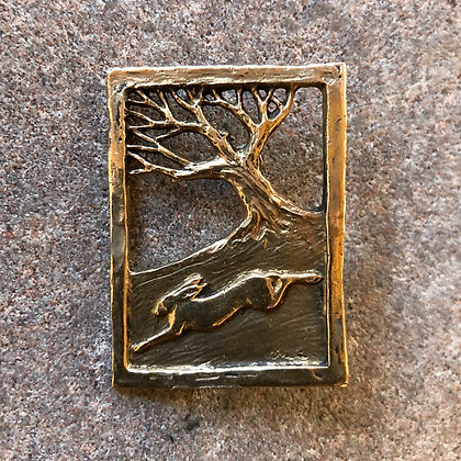Hare running through wood brooch in bronze