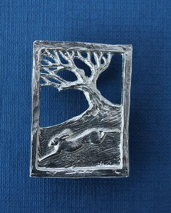 Hare running past tree brooch
