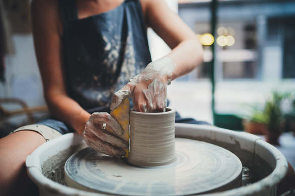 Cropped Image of Unrecognizable Female Ceramics Maker working with Pottery Wheel in Cozy W