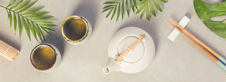 Asian food background - tea and chopsticks on a grey concrete background. Top view, flat l
