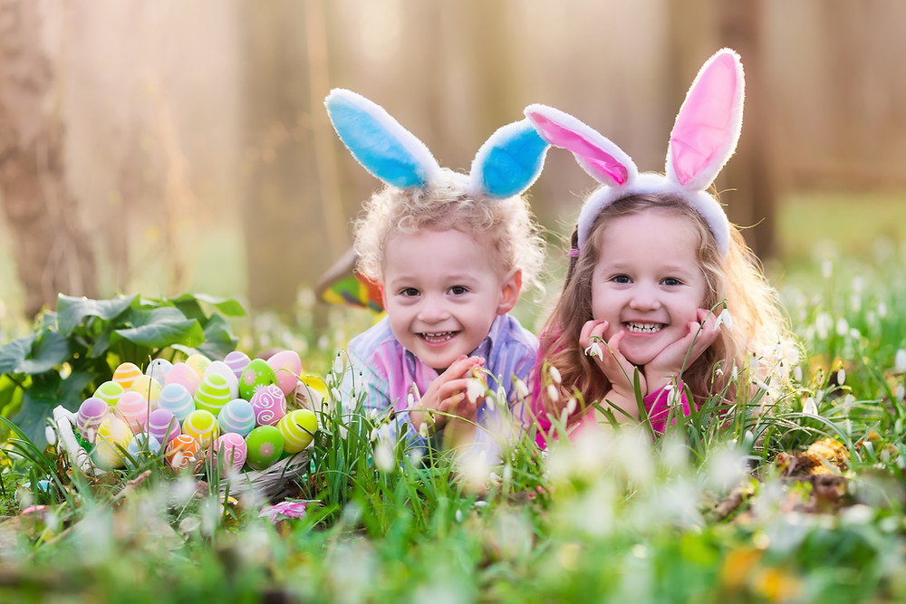 Two little girls wearing bunny ears in the garden