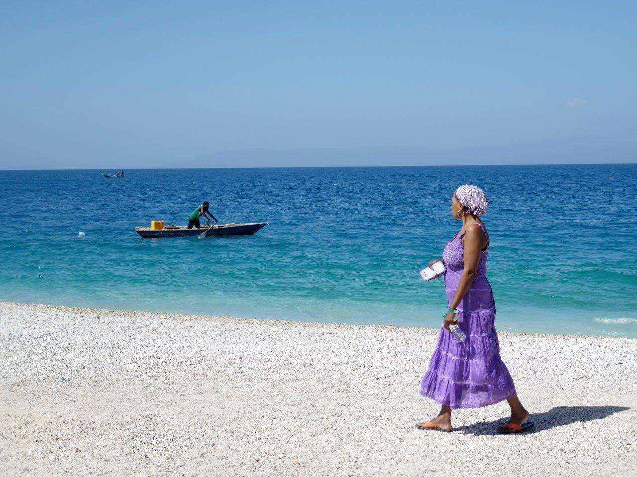 Woman walking on Kaliko Beach with fisherman in background