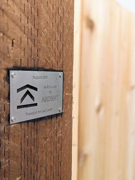 Stainless steel branding plate for a custom cedar fence