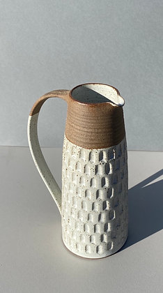 Stoneware jug with white glaze and carved pattern