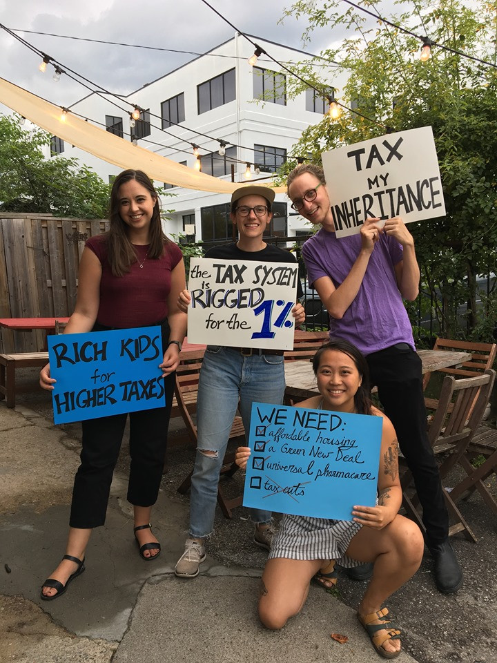 "Four Resource Movement members hold signs saying ""Tax My Inheritance"" and ""Rich Kids for Higher Taxes"""