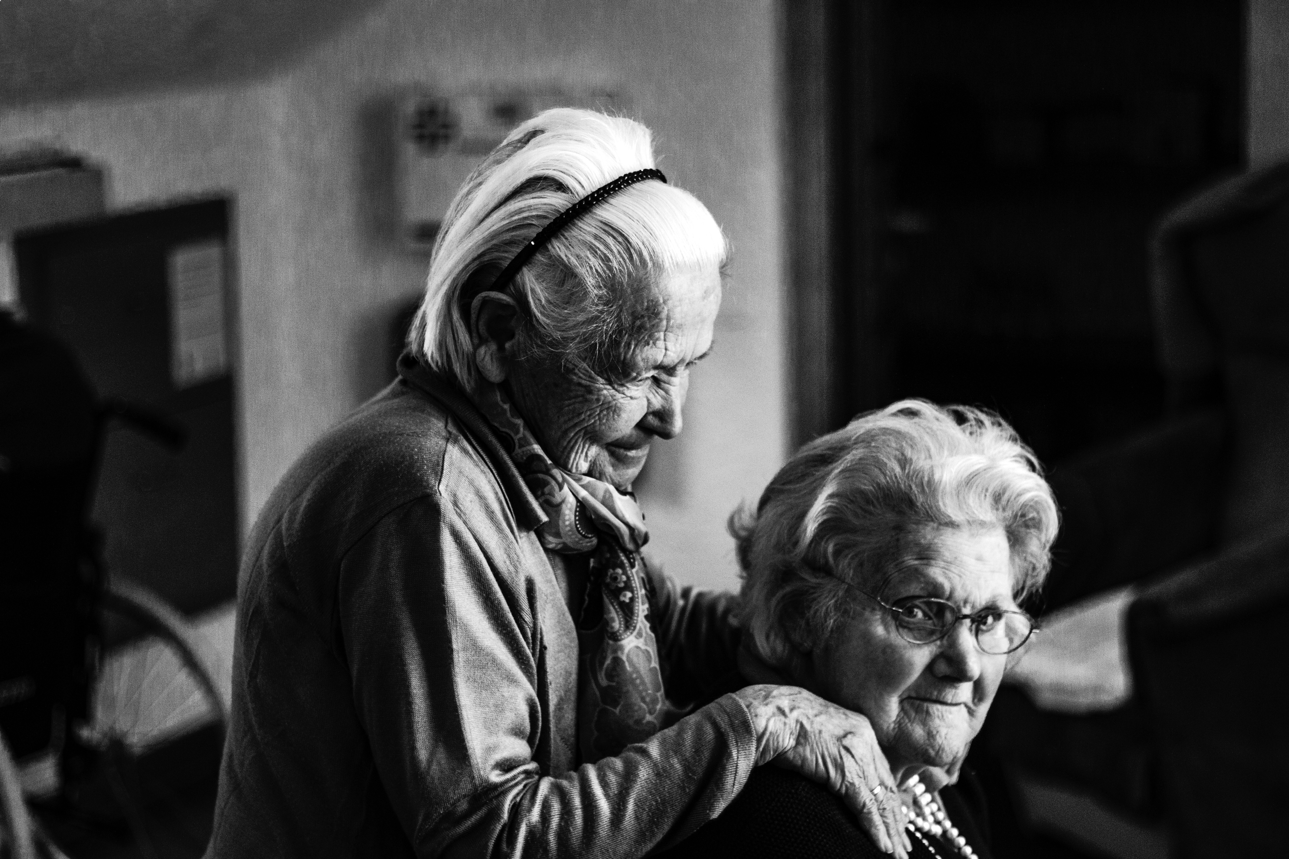 Two elderly women with hands on shoulder