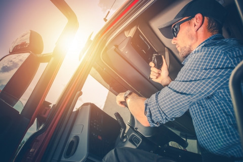 Male truck driver inside truck holding cb radio speaker with sun in background