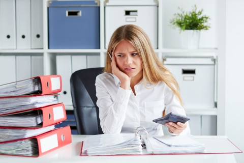 frustrated blonde woman at desk with stack of binders