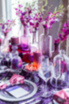 Purple Dendrobium Orchids in Purple Glass Bottles with Purple Votives and Purple and Fuschia Moon Series Carnations Photo Credit: Sharon Nicole Photography #BBJ #EventDesign #PoshAndPrivate