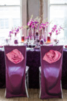 Purple Chair Covers with Pink Rosette Accents with Purple Rosette Linen and Purple Dendrobium Orchid Flowers in Purple Glass Bottles Photo Credit: Sharon Nicole Photography #WildflowerLinens #Event Design #PoshAndPrivate