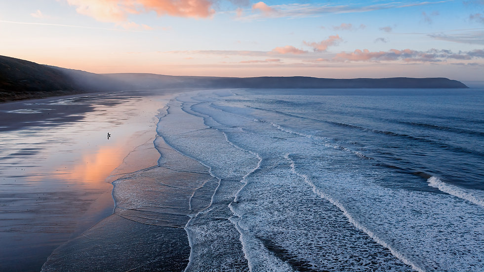 Aerial view of Woolacombe beach  and Baggy Point at dawn, waves breaking on a beach where