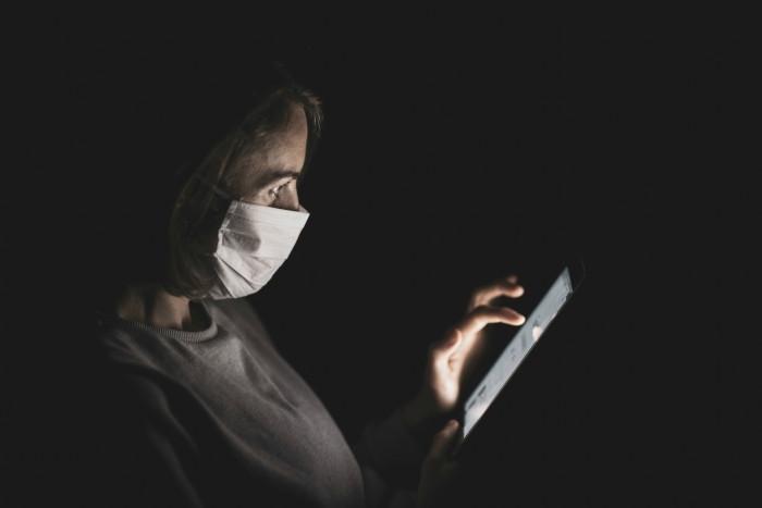 Mulher de máscara mexendo no celular