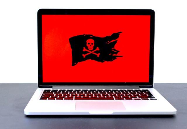 notebook com símbolo pirata na tela