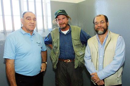 El ministro Ronnie Kasrils, earthwalker Paul Coleman y el concejal de Ciudad del Cabo, Brian Watson, dentro de la celda de la prisión Robben Island de Nelson Mandela