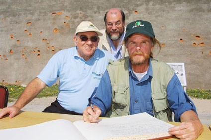Earthwalker Paul Coleman signing the Robben Island Guest Book, with SA Minister Ronnie Kasrils (seated) and Councillor Brian Watson.