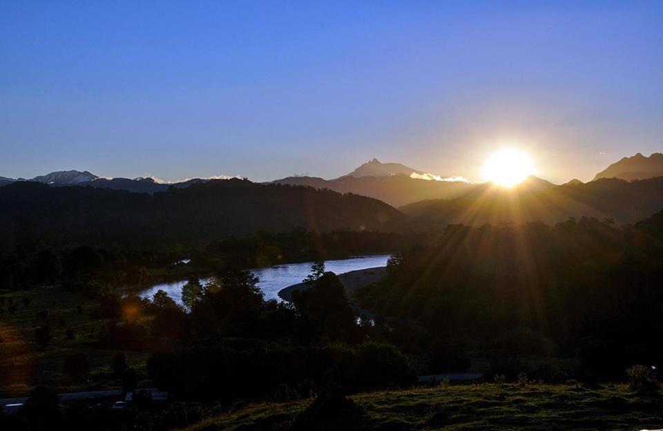 En un buen día de verano, el sol se pone en Melimoyu y el río Palena.