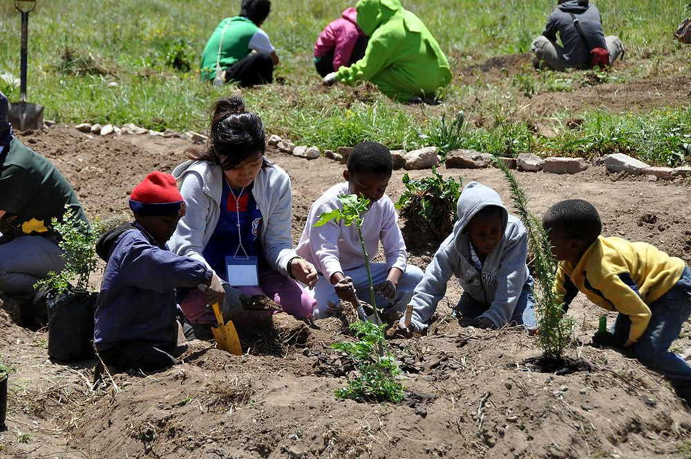Japanese Volunteer and South African Children creating a Permaculture Food Garden