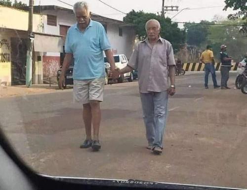 Idoso anda de mãos dadas com amigo deficiente visual para ajudá-lo em sua caminhada diária