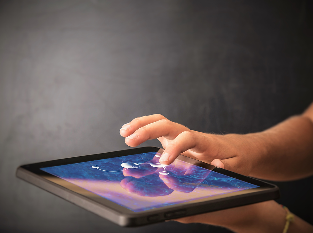 A person is holding a tablet with one hand below the screen and the other hand exploring the screen. The index finger is being used to feel haptics in the image on the tablet screen.