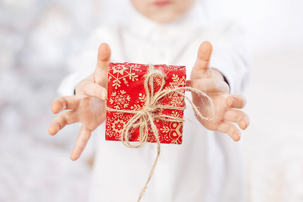 Child hands holding  gift box wrapped in