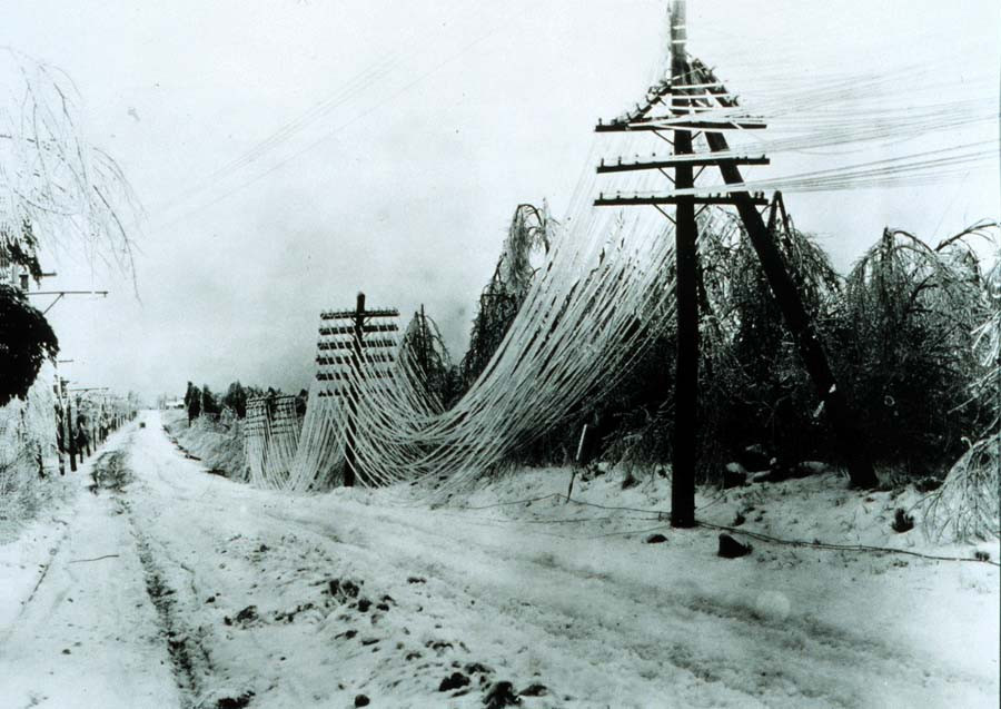 This is a black and white photo that shows a landscape following an ice storm. A road runs from foreground on the viewer's right to the horizon on the left hand side of the photo. A set of powerlines run alongside the road, supported by old-style wooden poles with glass insulators. Dozens of wires are caked with ice and sag to the ground under the weight of the frigid conditions. The image is in the public domain, courtesy of the United States National Oceanic and Atmospheric Administration.