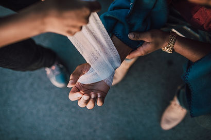 First aid being performed on a hand, Gauze being wrapped around wounded hand