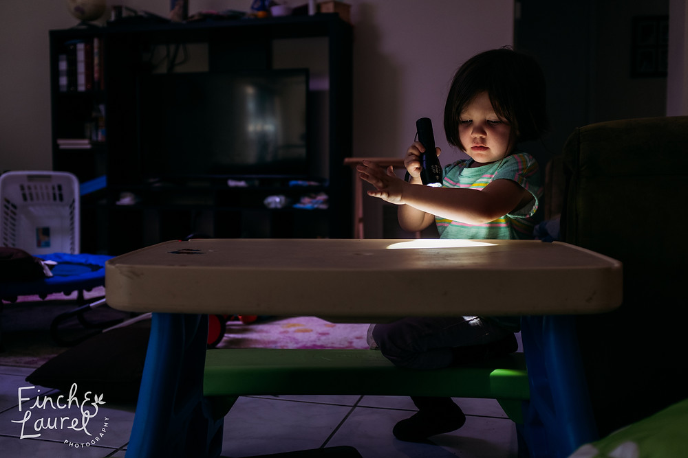 A little girl shines a flashlight on her arm and looks at it with wonder during a documentary family photography session in Jacksonville, Florida.