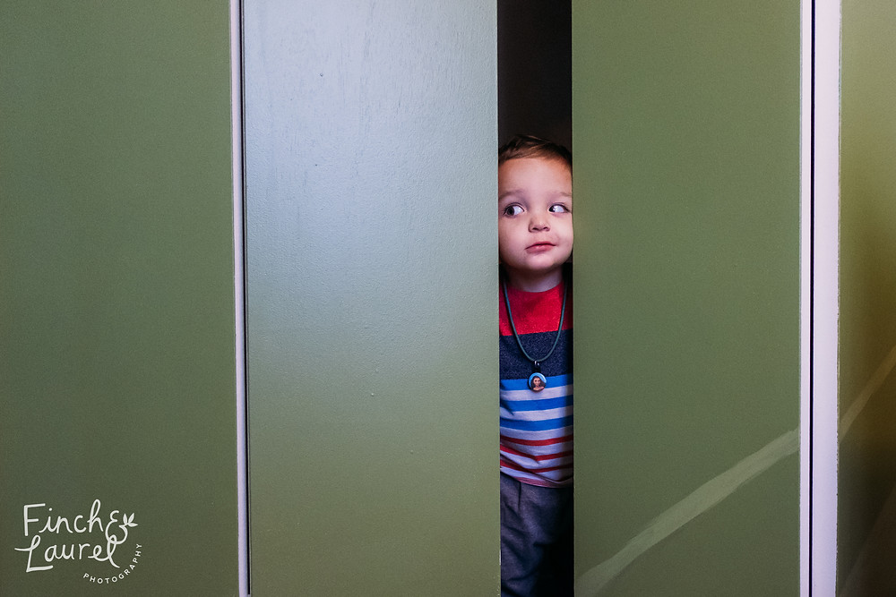 A toddler boy peaks his head out of the closet with a silly face during a documentary family photography session in Jacksonville, Florida.