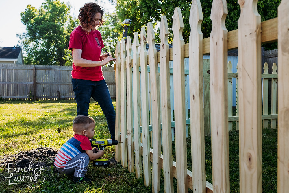A mother works on building a fence while her toddler son holds a drill during a documentary family photography session in Jacksonville, Florida.