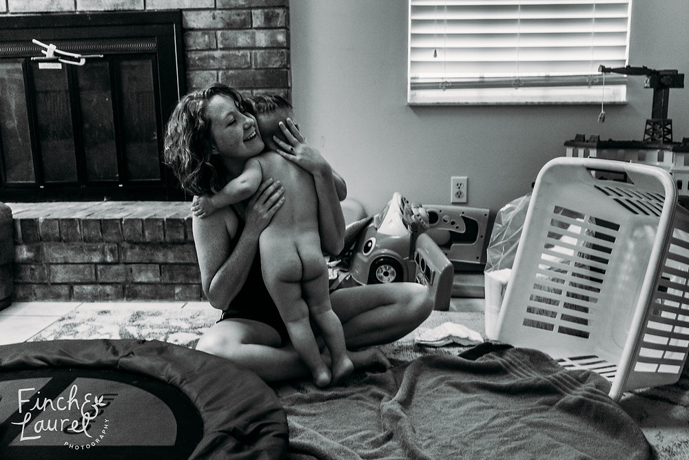 A mother embraces her toddler son after bath time during a documentary family photography session in Jacksonville, Florida.