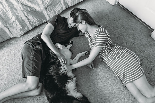 Chelsea, the family photographer behind Finch and Laurel Photography, lays on the floor with her husband and dog in their home in Jacksonville, Florida.